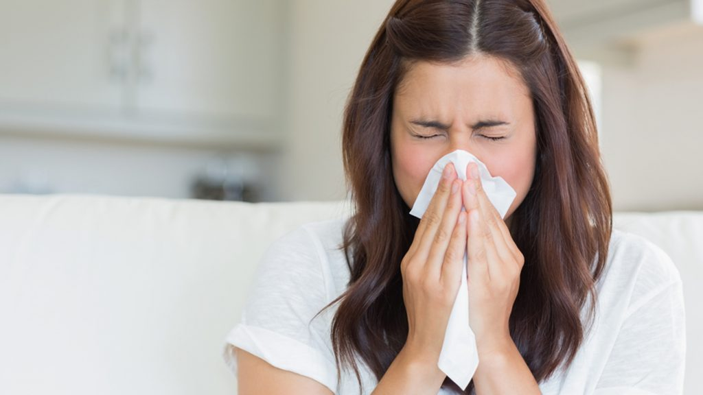 Brunette sneezing in a tissue in the living room; Shutterstock ID 114498919; PO: today.com